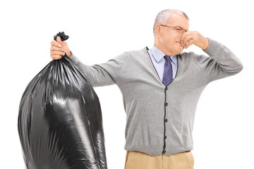 Senior holding a stinky garbage bag