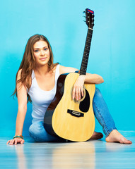 Young woman musician with guitar sitting on a floor.