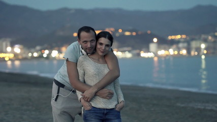 Portrait of happy couple hug on beach in the evening