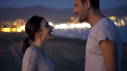 Couple talking and flirting on beach at night