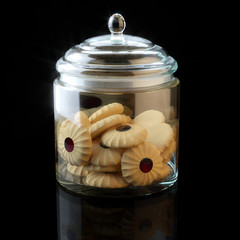 Glass jar full of chocolate cookies on black background