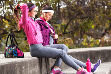 Two attractive female sitting and preparing for jogging.