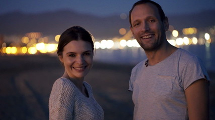 Portrait of happy, smiling couple on beach at night