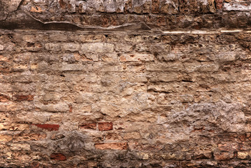 old brick wall with loose bricks and deteriorating mortar