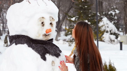 Woman playing with snowman