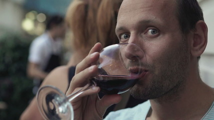 Portrait of happy man drinking red wine in cafe