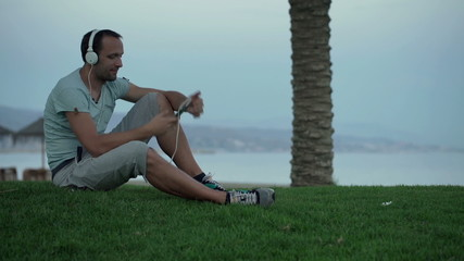 Young man listening to music sitting on grass by sea