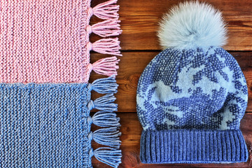 Beautiful knitted scarf and hat with fur pompon on a wooden text