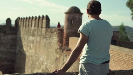 Attractive man admire ancient castle ruins