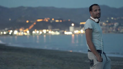 Happy, young man looking around on beach in the evening