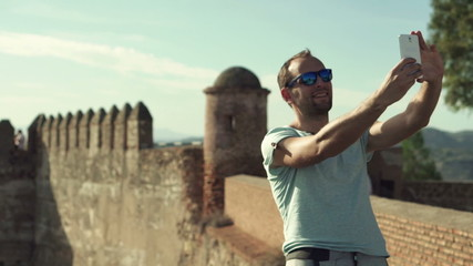 Tourist taking selfie photo with cellphone near ancient castle r