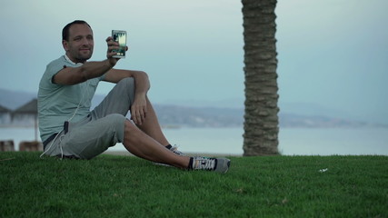 Happy man taking selfie photo with cellphone sitting on grass by