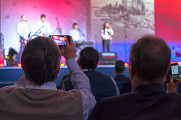 people making video record of the concert