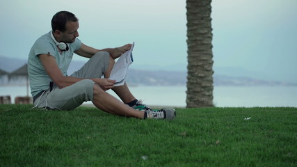 Attractive man reading newspaper sitting on grass by sea