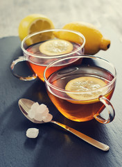 Two cups of tea with lemon and sugar for break