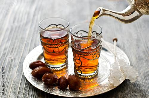Poster Traditional arabic tea with dates and sugar on a plate