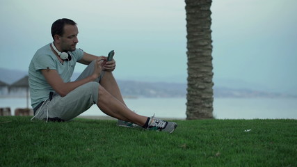 Handsome man using smartphone while sitting on grass by sea