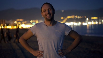 Portrait of happy, smiling man standing on beach at night