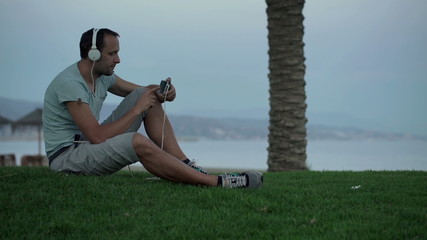 Young man watching movie on smartphone sitting on grass by sea