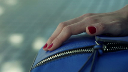 Close up of woman fingers tapping handbag