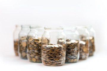 coins in a three glass jars against a white background