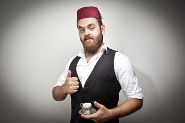 Man in traditional turkish hat dress kabadayi drinking coffee