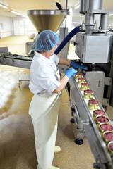 Lebensmittelindustrie - Frau am Fliessband von Wurstkonserven