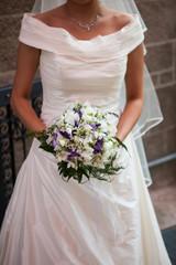 La sposa cammina con il bouquet fra le mani