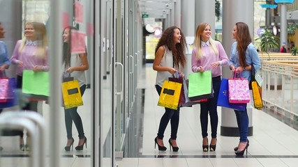 Three beautiful girls with shopping bags watch purchase on
