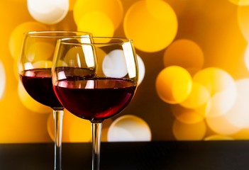 red wine glasses on wood table on golden bokeh lights background