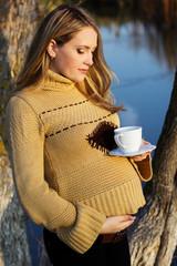 Pregnant woman on the autumn lake