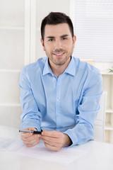Lachender junger Mann sitzend im Büro