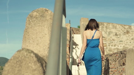 Woman looking and walking through ancient castle ruins