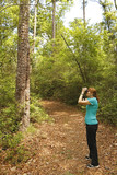 Woman with Binoculars Birdwatching on a Forest Trail poster