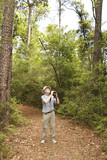 Man with Binoculars Birdwatching on a Forest Trail poster