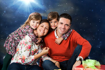 Happy family portrait with presents at christmas.