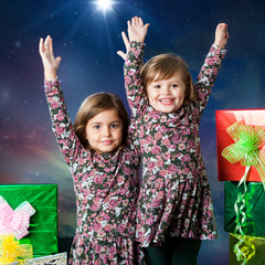 Two happy kids raising hands next to presents.