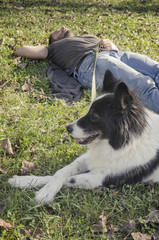 Man laying in the grass with his dog
