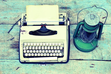 Retro typewriter with vintage lamp on wooden background