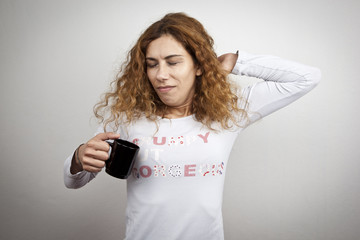 Tired sleepy yawning woman waking up with cup of coffee