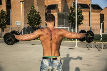Back of Attractive Muscular Hunk Man Lifting Weights Outdoor