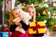 Kinder an Heiligabend mit Weihnachtsgeschenken