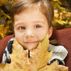 Little boy laying on leafs