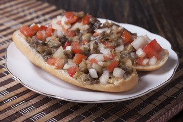 Eggplant with tomato and onion on white bread.