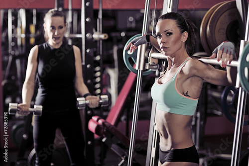 Poster Fitness Two sporty woman workout in the gym