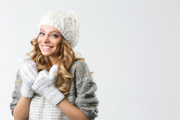 Portrait of beautiful happy girl in sweater hat and mittens