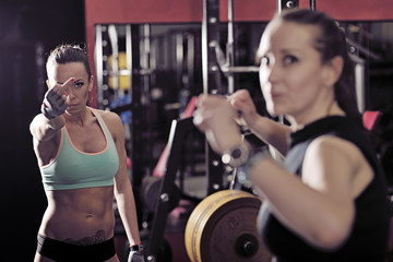 Two sporty woman talking in the gym