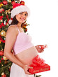 Pregnant  woman holding Christmas box.