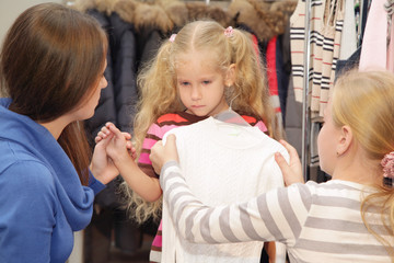 Family chooses clothes in shop
