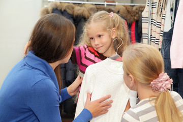 Mum with a daughter in clothes shop